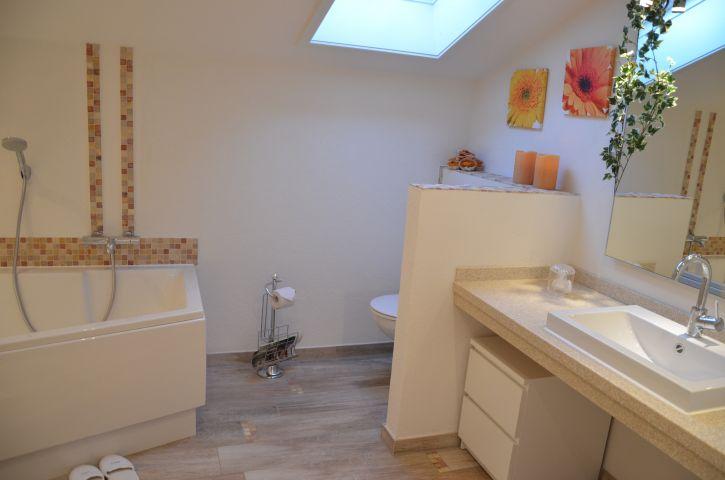 Großes Bad mit Wanne und Dusche, WC hinter Mauer