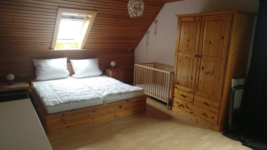 Schlafzimmer mit Kinderbett im Obergeschoss