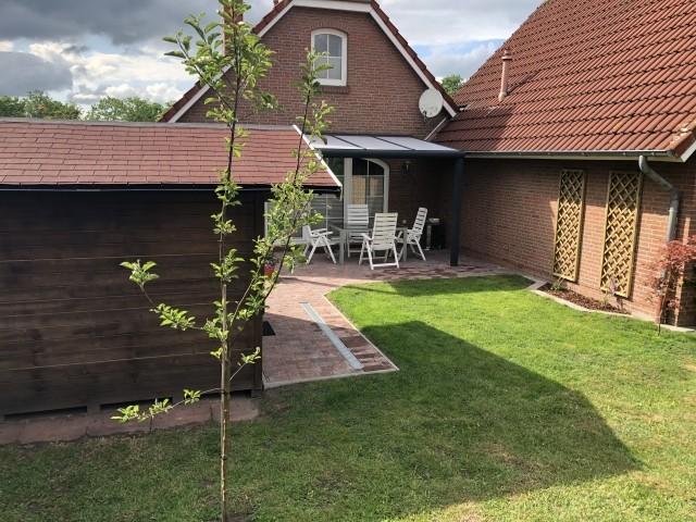 Blick vom Garten auf die überdachte Terrasse