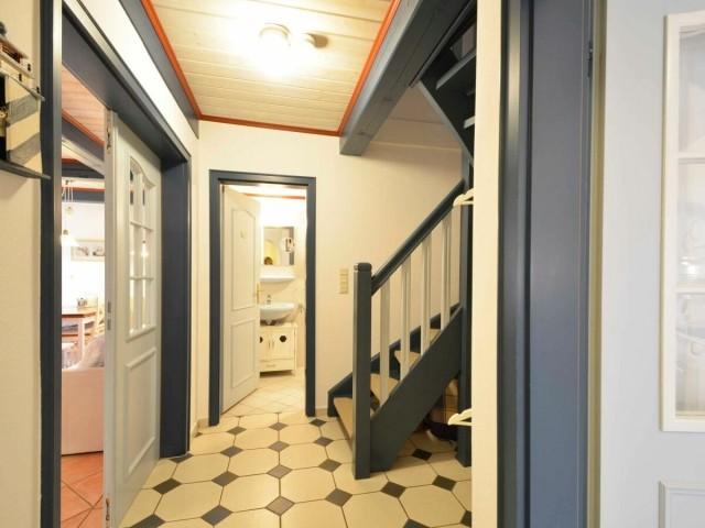 Eingangsbereich in der Unteren Etage - links geht es in Wohnzimmer, geradeaus ins Badezimmer und auf der Treppe in die Erste Etage und rechts geht es in die Küche.