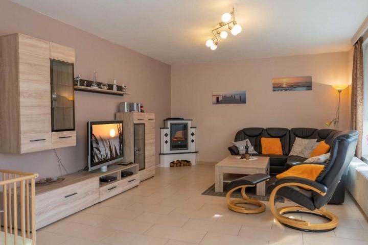 Lichtdurchfluteter Wohnbereich mit Elektrokamin und Sitzecke