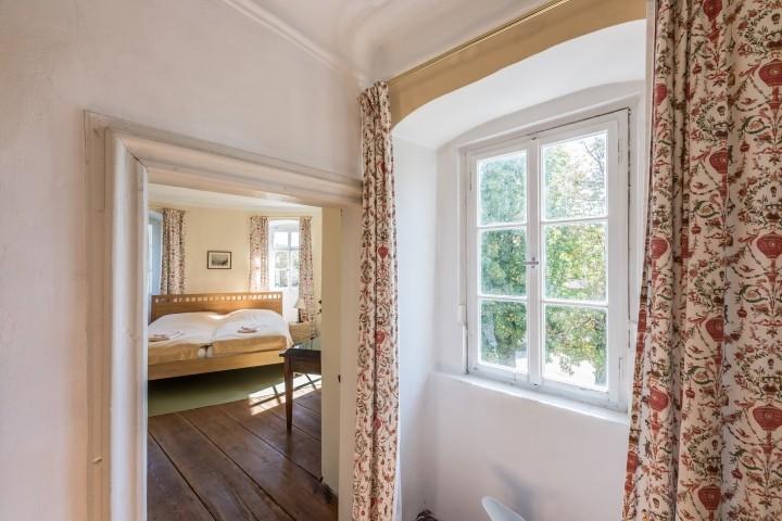 Blick aus dem Wohnzimmer mit geschmackvollen Vorhängen ins Schlafzimmer