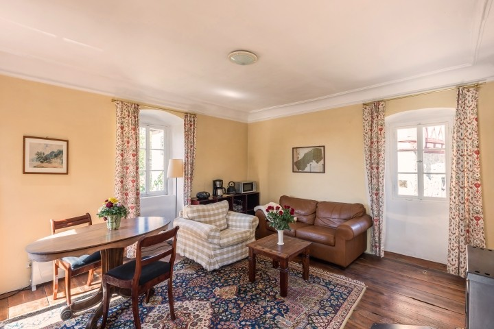 Das gemütliche Wohnzimmer mit Esstisch, Sofaecke und Kaminofen