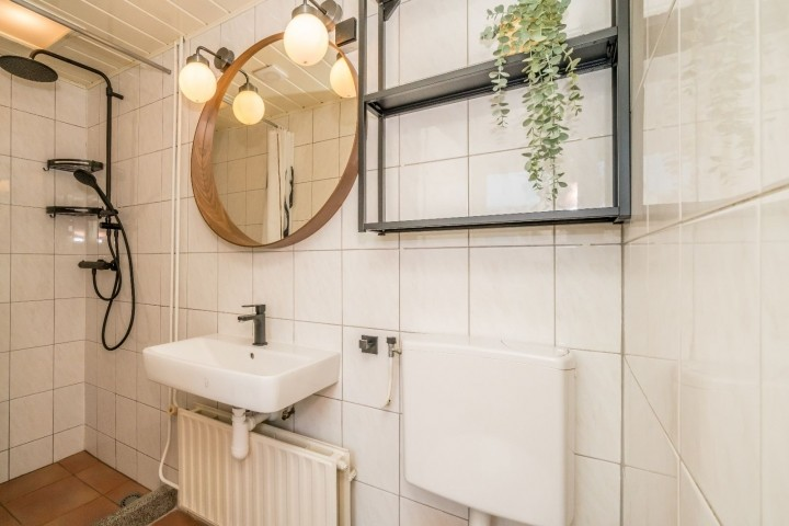 Badezimmer mit Regendusche, Toilette und Waschbecken