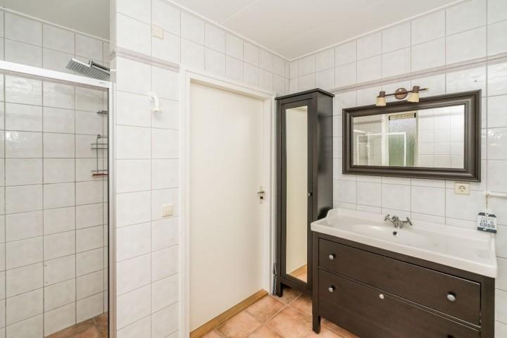 Das Badezimmer mit Dusche, Badmöbel und Toilette