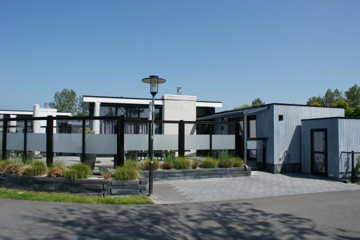 Chalet mit Terrasse, Pkw-Stellplatz, Hundedusche  und Gartenhaus und Außenansicht
