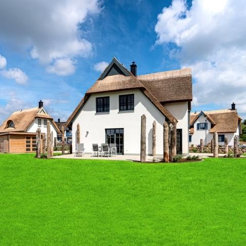 Hausansicht mit Terrassen und Gartenhaus
