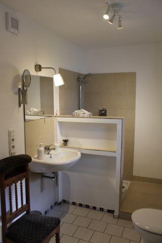 Das Bad mit ebenerdiger Dusche und Fenster