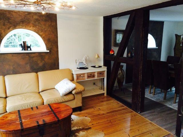 Wohnzimmer mit offener Balkenlage zum Essbereich