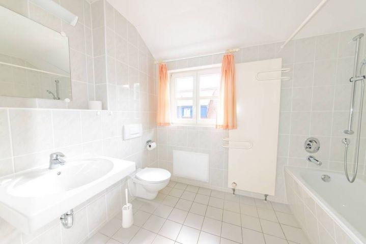 Das große und moderne Bad erwartet Sie mit Badewanne und Fenster.