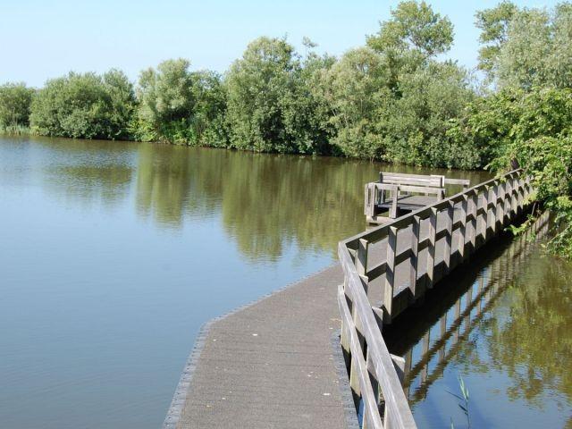 See mit Holzbrücke vor der Terrasse