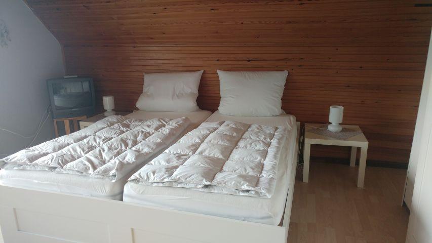 Schlafzimmer im Obergeschoss mit Zugang zum Balkon und Schleiblick