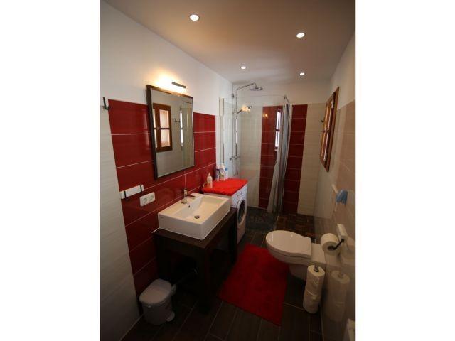 Modernes Badezimmer mit WC, Raindrop Shower und Waschmaschine.