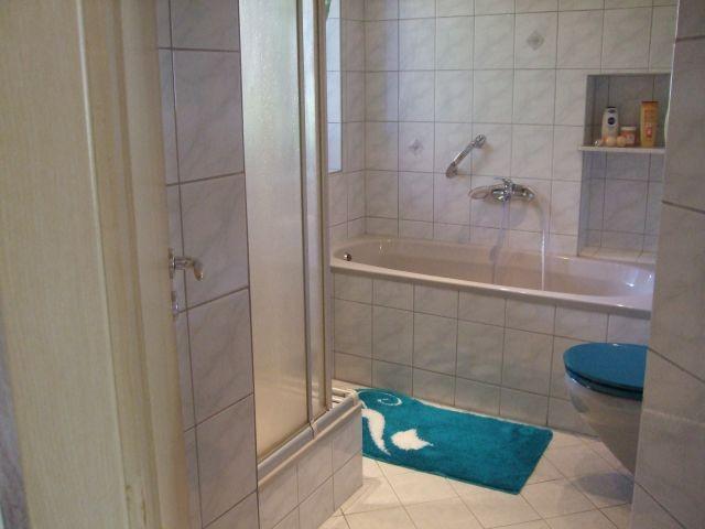 Badezimmer mit Dusche, Badewanne, Waschbecken, WC, Pflegeprodukten