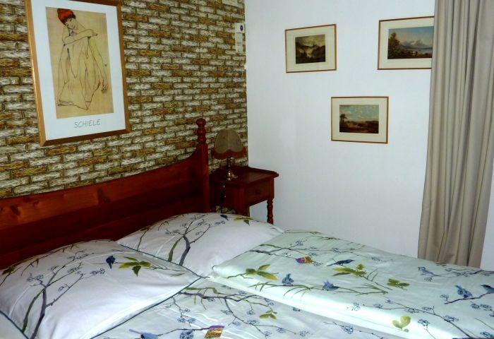 Schlafzimmer 1 mit Doppelbett und Vorraum mit Kinderbett