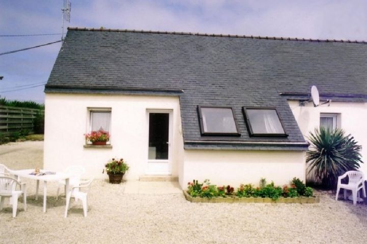 Ferienhaus mit eingezäunten Garten, Terrasse, Gartenmöbel und Sonnenliegen.
