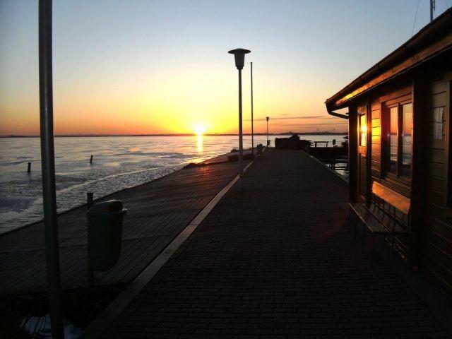 Sonnenuntergang bei zugefrorenem See am Bootsanleger der Segelschule Schlick