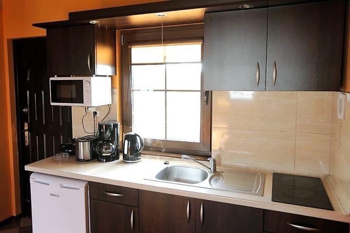 Zu der Ausstatung der Küche gehören Elektroherd, Wasserkocher, Mikrowelle, Kaffeemaschine, Toaster, Sandwich, Kühlschrank mit kleiner Gefriertruhe, Spüle,Küchengrundausstattung (Becher, Teller, Besteck, Töpfe, Gläser).