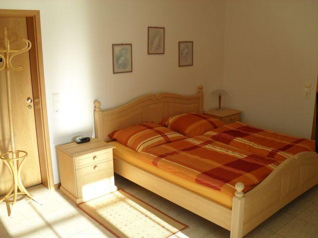 Schlafzimmer mit Doppelbett, Nachttischchen und TV