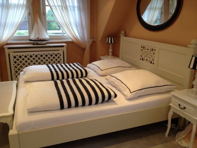 Stimmig bis ins letzte Detail: Schlafzimmer mit großzügigem Doppelbett, Kommode und Holz-Kinderbett
