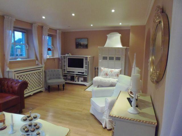 Antiker Kachelofen und weißer Flat-Screen-TV im Wohnzimmer