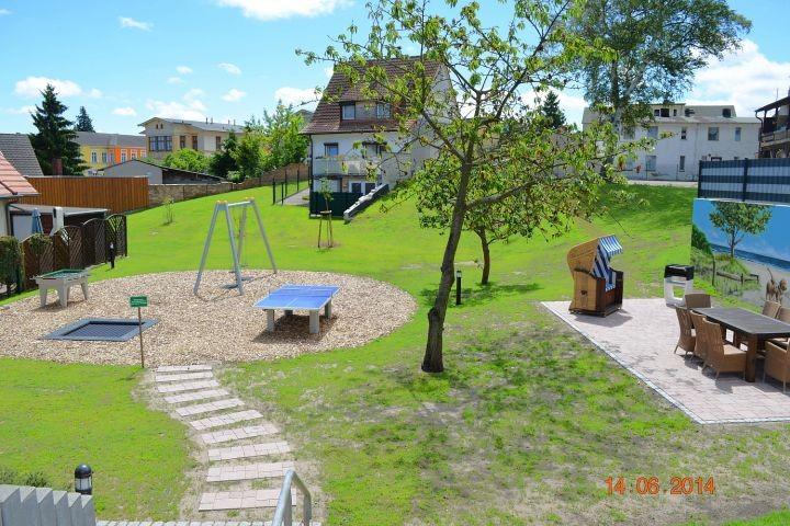 Blick vom Haus in den Garten mit Grill- und Spielplatz