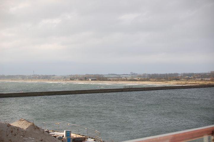 Blick auf die Hafeneinfahrt und den langen Sandstrand mit Hunde, Bade, Kitesurf und FFK Bereichen