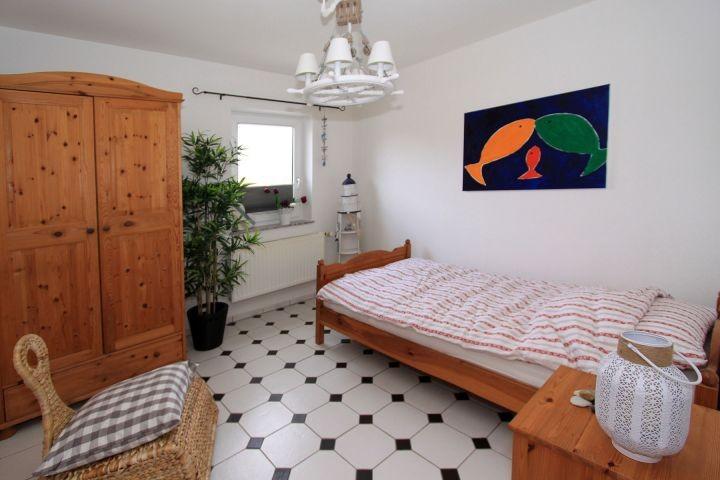 Schlafzimmer mit Einzelbett, Nachttisch und  Schrank