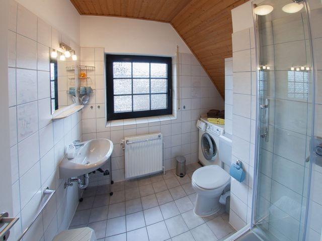 Helles Duschbad mit Fenster und Waschmaschine