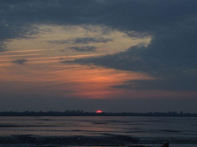 Der Feuerball versinkt hinter Wilhelmshaven