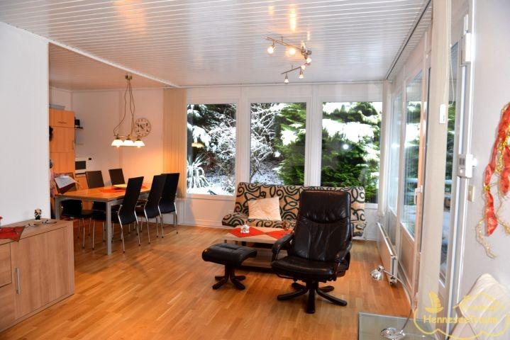 Wohnzimmer mit großen Fenstern und Blick in den Garten