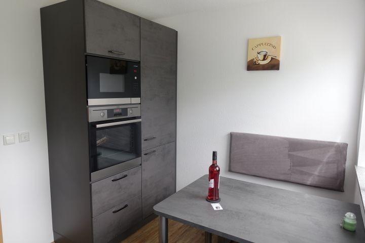 Küche mit Mikrowelle und Backofen