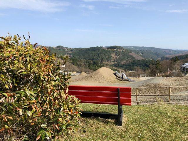 Eine Bank im Garten lädt zum genießen des Panoramablicks ein
