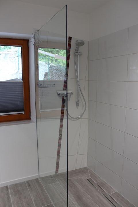 Badezimmer mit ebenerdiger Dusche und Fenster