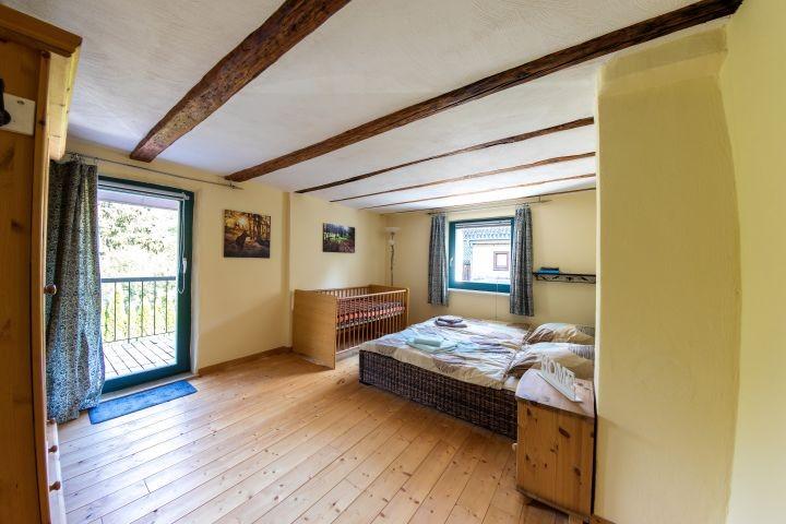 Schlafzimmer 1 mit Kinderbett , Doppelbett und Balkon