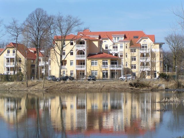 Idyllische Süd-Ansicht des Dünenschlosses mit Blick auf einen kleinen See und den Stadtwald