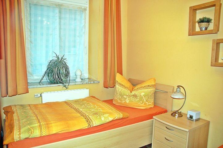 Schlafzimmer mit Fenster und zwei separaten Einzelbetten.