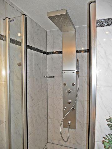 Komfortables Marmor-Badezimmer mit tropischer Regendusche und Massagedüsen....