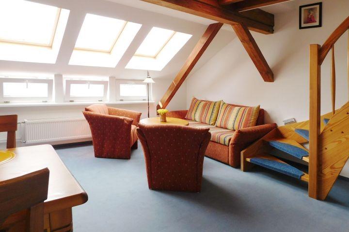 Wohnbereich mit Schlafcouch und Sessel