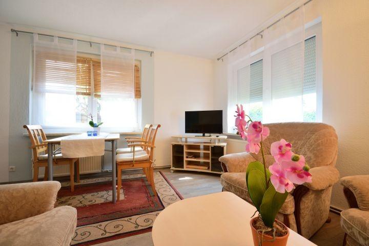 Wohnzimmer mit Sofalandschaft, Esstisch und Sat-TV