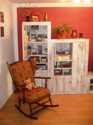 Wohnzimmer mit Schaukelstuhl, Büchern, Spielen, Regionsinfo