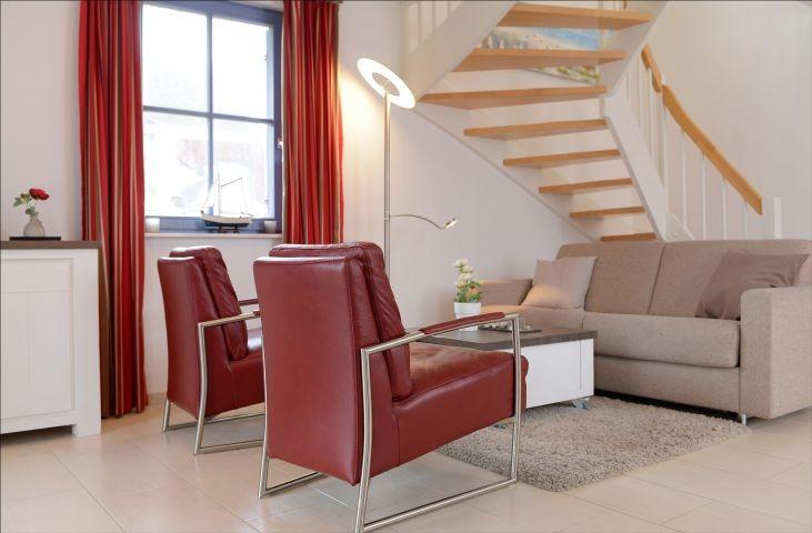 Wohnbereich mit Schlafsofa und Treppe ins Obergeschoss