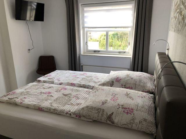 Schlafzimmer im EG mit Boxspringbett und Flat-TV