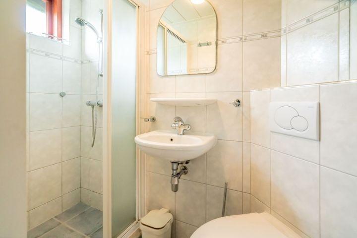Badezimmer mit Dusche, Waschbecken und Toilette
