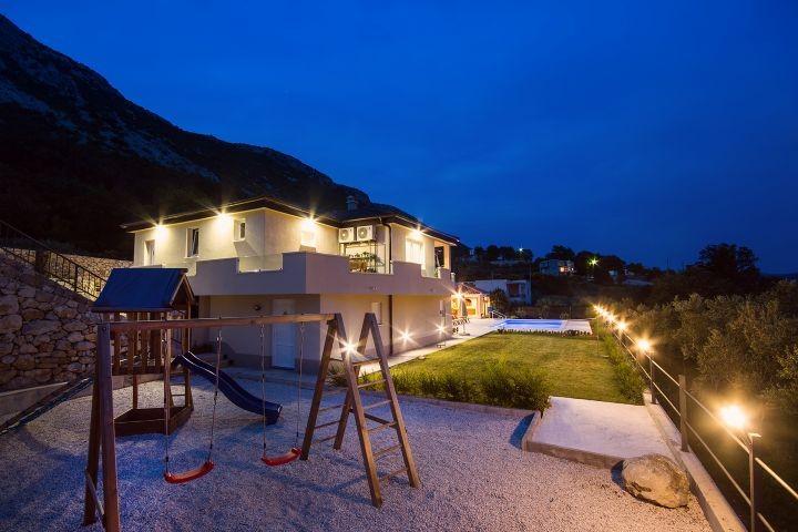 Spielplatz nachts mit Rutsche, Holzhaus und Kletternetz