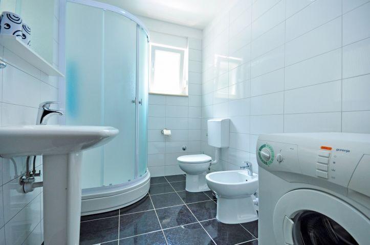 grosses Badezimmer mit Dusche und Waschmaschine