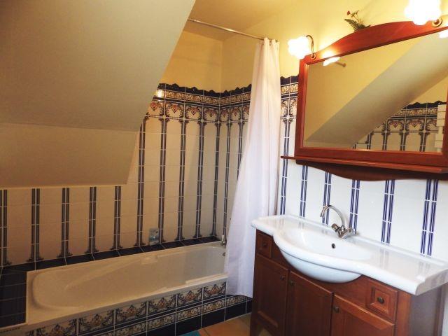 Das Badezimmer mit Badewanne und Duschvorrichtung
