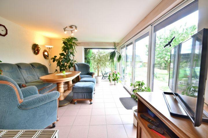 Wintergarten mit Sofalandschaft, TV und Ausblick in den Garten