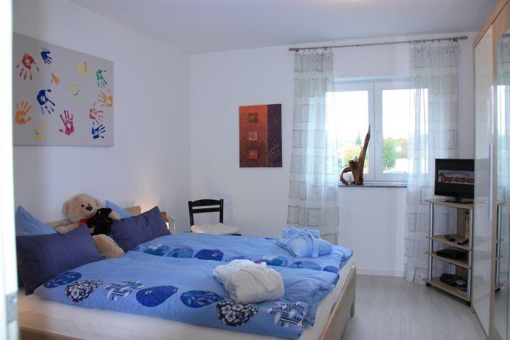Schlafzimmer mit Fernseher und großem Kleiderschrank