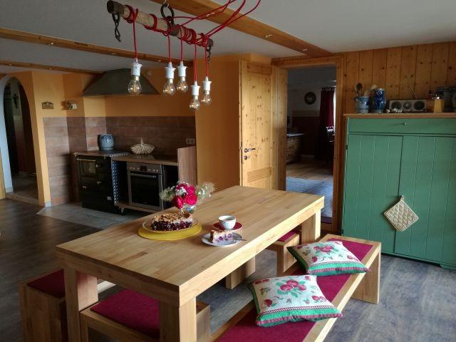 Küche mit gemütlichem Essplatz, Herd und Holzbeistellherd, Blick ins Schlafzimmer